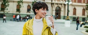 Young woman outside holding a cup of coffee
