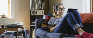 Woman sitting on her couch in her living room, reading on her tablet