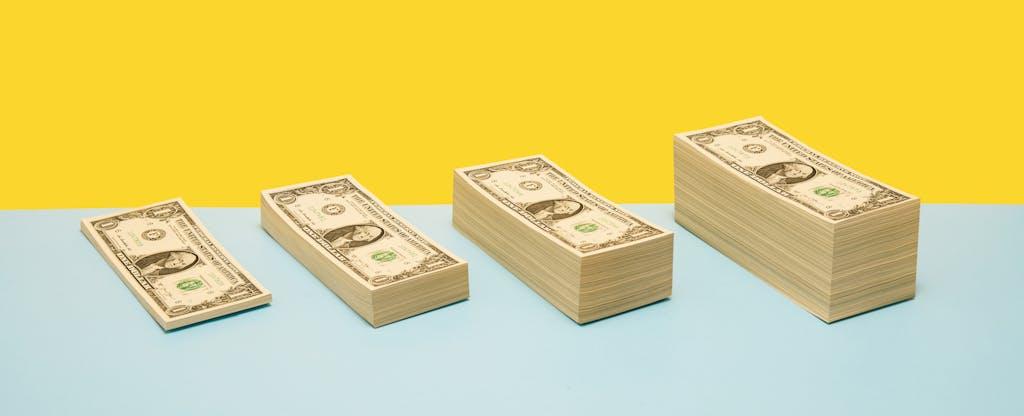 4 various sized stacks of US 1 dollar bills arranged in ascending order on blue shelf, yellow background
