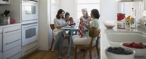 Multi-generational group of female family members gathered in their kitchen, talking and laughing together