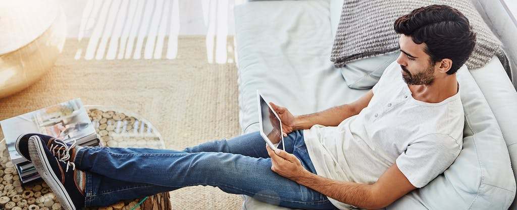 Man sitting on the couch in his living room, reading on his tablet