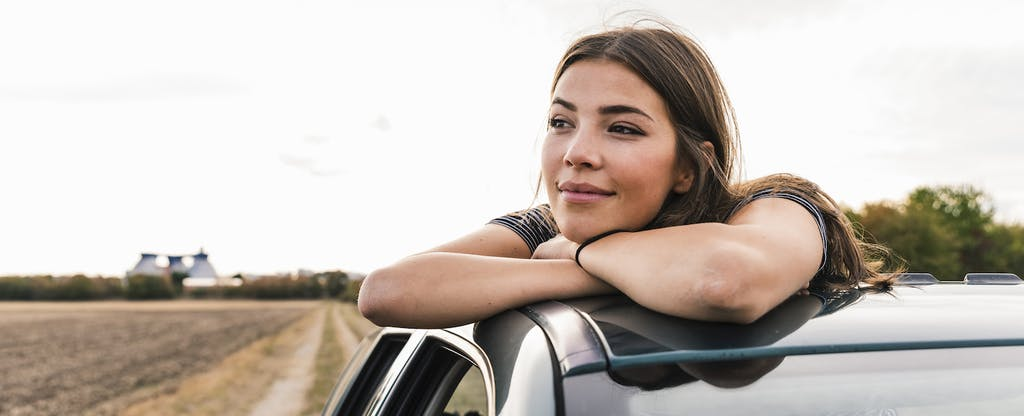 Woman leaning out of the sun roof of her car, thoughtfully looking into the distance