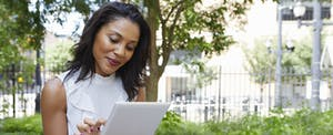 Woman sitting outside in a city park, looking at her tablet and smiling