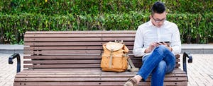 Man sitting on a park bench, reading on his tablet