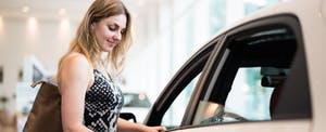 Young woman thinking about buying a rental car