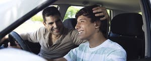 Teenage boy driving a car with his dad in the passenger seat, both of them are smiling