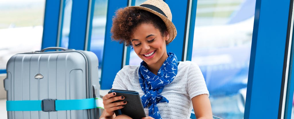 Smiling girl at the airport, sitting next to her suitcase and looking at digital tablet