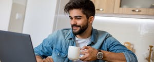 Young man drinking coffee and looking at laptop in his kitchen