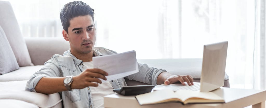 Young man looking at bills and preparing to mail a credit card dispute