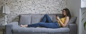 Woman lounging on her couch, using her smartphone