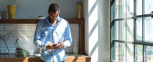 Man standing in his kitchen, reading on his phone