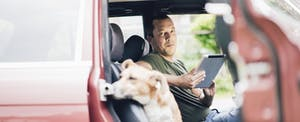 Man sitting in his car, holding a tablet, and looking over at his dog sitting in the passenger seat