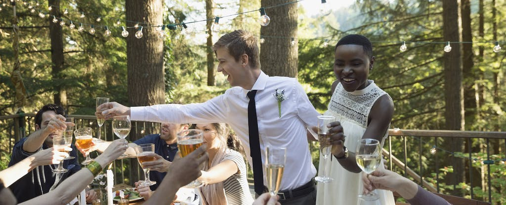 Bride and groom standing together at their wedding reception, giving a toast