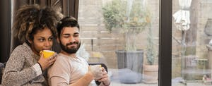 Man and woman sitting together on their couch, drinking coffee and smiling