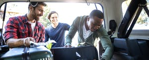 Three male friends packing the car for a road trip