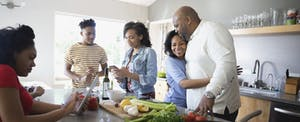 Adult family members standing together in their kitchen, cooking, talking and laughing