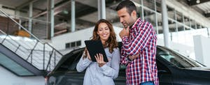 Young couple at car dealership looking at new car together
