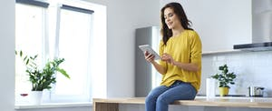 Woman sitting on her kitchen counter, reading a review of ACE Cash express loans on her tablet