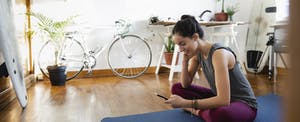 Young woman with smartphone on yoga mat in apartment feeling less anxious about the upcoming tax season