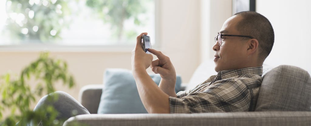 Man sitting on his couch at home in his living room, using his phone to read a review of Bright Lending