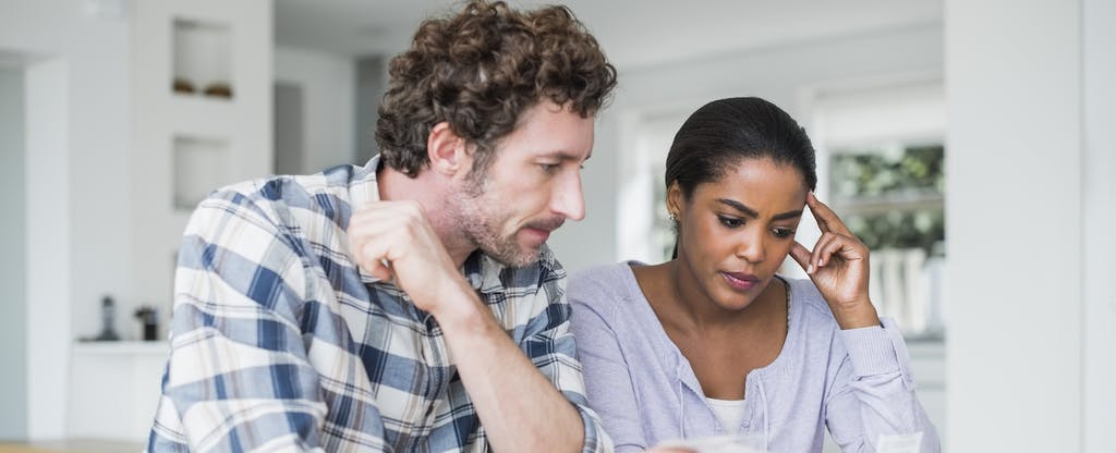Couple sitting together at their kitchen table, reading about how to get a car loan if you're unemployed