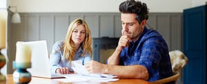 Couple sitting at kitchen table with bills, wondering if they can get an emergency loan with bad credit