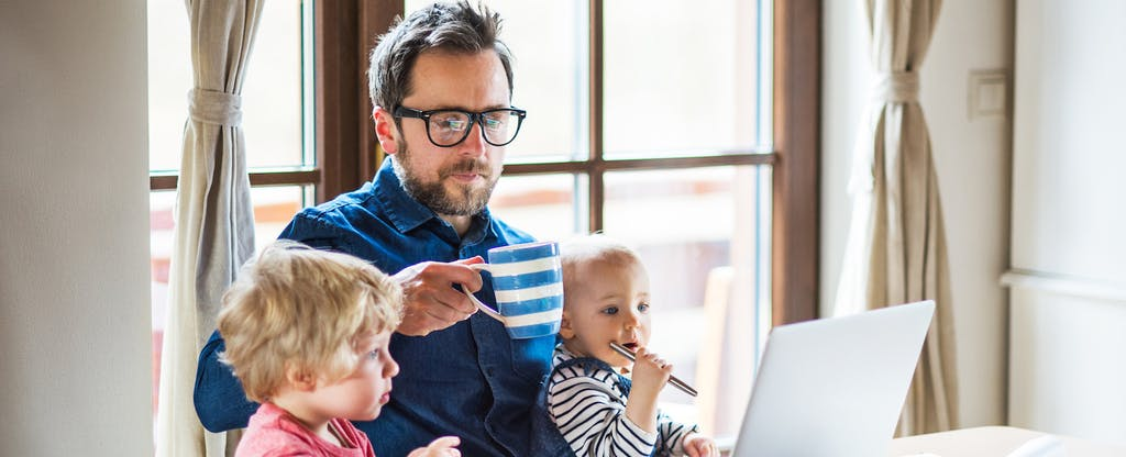 Man sitting at a table with his young children. He has his laptop open and is reading about Form 8889.