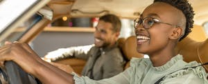 Young, smiling couple in car talking about full coverage auto insurance
