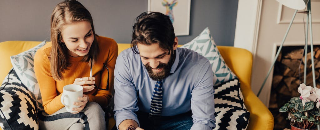 Man and woman sitting together on their couch, smiling and talking to each other about whether to get a HELOC vs. a home equity loan