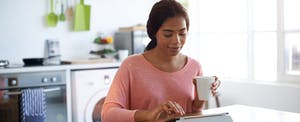 Young woman in her kitchen using a tablet to track her NJ tax refund