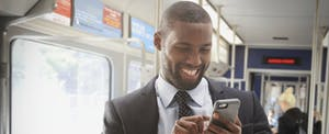 Man standing on a bus, smiling and reading on his smartphone about no-fee banking