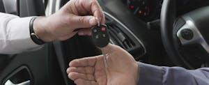 Close up of two hands - car salesman handing keys to car buyer