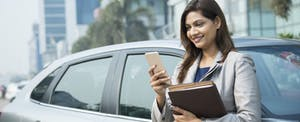Businesswoman standing next to car with cellphone, looking up rental car insurance coverage on her credit card