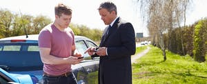 Two men standing next to their cars, exchanging car insurance information after getting into a minor car accident