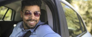 Man wearing sunglasses and sitting in car, thinking about rental car insurance