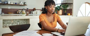 Young woman on laptop at kitchen table, thinking about taking out a 401(k) home loan