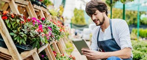 Business owner of a garden center looking up the blue business cash card on his digital tablet