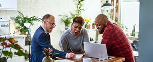 Couple sitting with a financial adviser in their kitchen, reading together about the best options for a personal loan with a co-signer