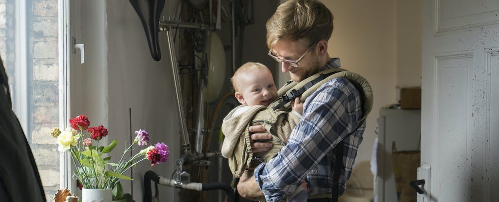 Young father holding his smiling infant in their kitchen