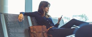 Woman sitting at the airport with her luggage, reading on her phone