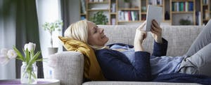 Woman relaxing on her couch, smiling and comparing car insurance rates on her tablet