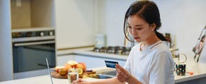 Woman using her laptop at home in her kitchen, holding her credit card in one hand
