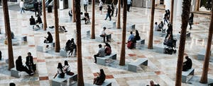 People sitting on benches in a mall lobby in New York