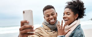 Man and woman standing together on a beach, smiling together for a selfie and showing off the new engagement ring on her hand