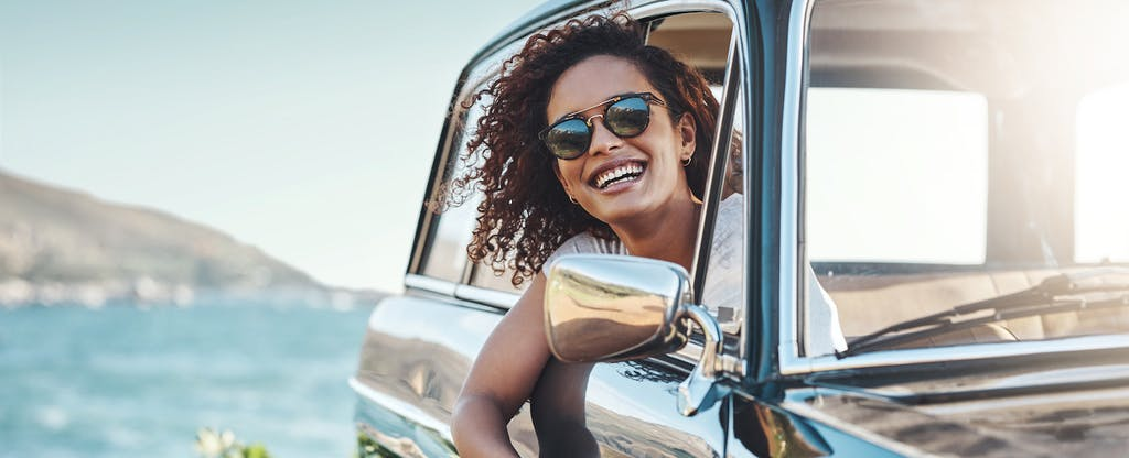 Woman sitting in her car, leaning out of the passenger side window on a sunny day, smiling