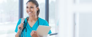 Happy female medical student thinking about applying for a laurel road personal loan to consolidate her debt