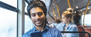 Young man sitting on a city bus, reading a review of TurboTax advance loans on his phone