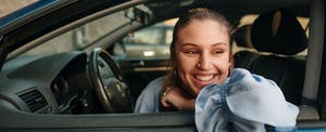 Young woman sitting in car, thinking about what types of auto insurance she should get
