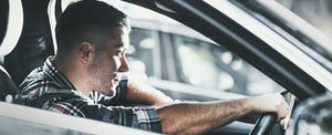 Young man driving car with a serious expression on his face