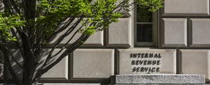 Photo of IRS building with a green-leafed tree at left